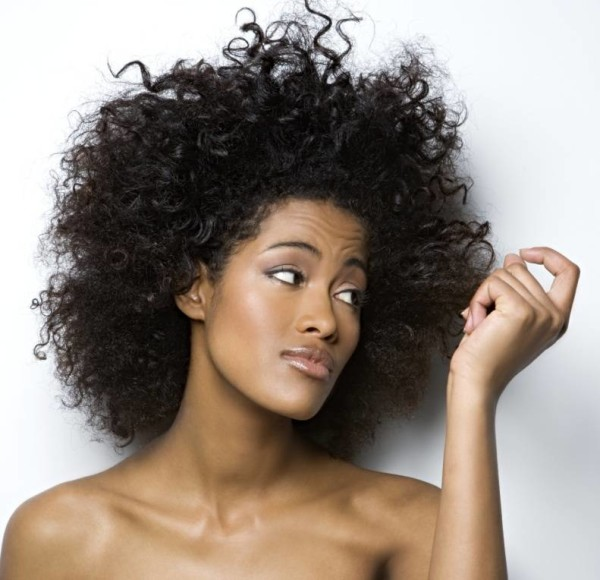 Young woman looking at her hair, close-up